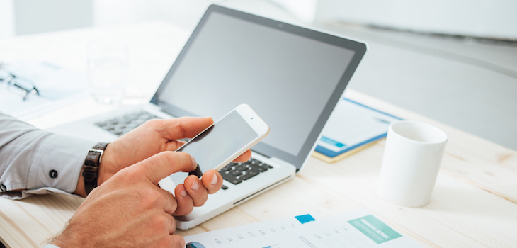 Businessman at desk using a financial app on his smart phone and working on reports, hands close up